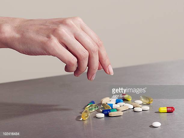 Woman reaching for pile of pills/tablets