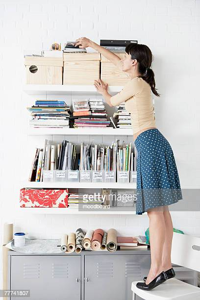 woman reaching for shelf - neat stock pictures, royalty-free photos & images