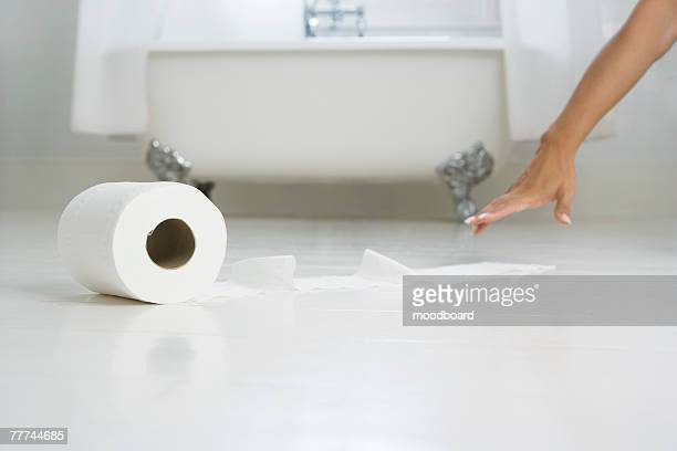 woman reaching for toilet paper roll on the floor - funny toilet paper stock pictures, royalty-free photos & images