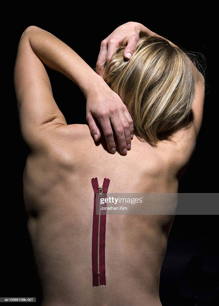 Woman reaching for zipper on back, studio shot : Stockfoto