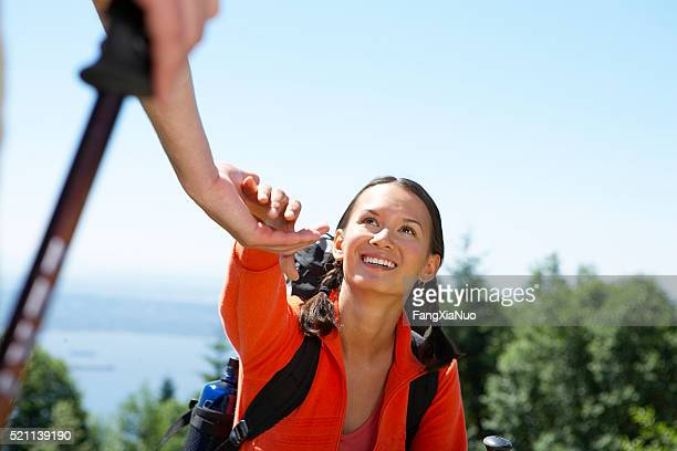 Woman reaching hand up for help while climbing