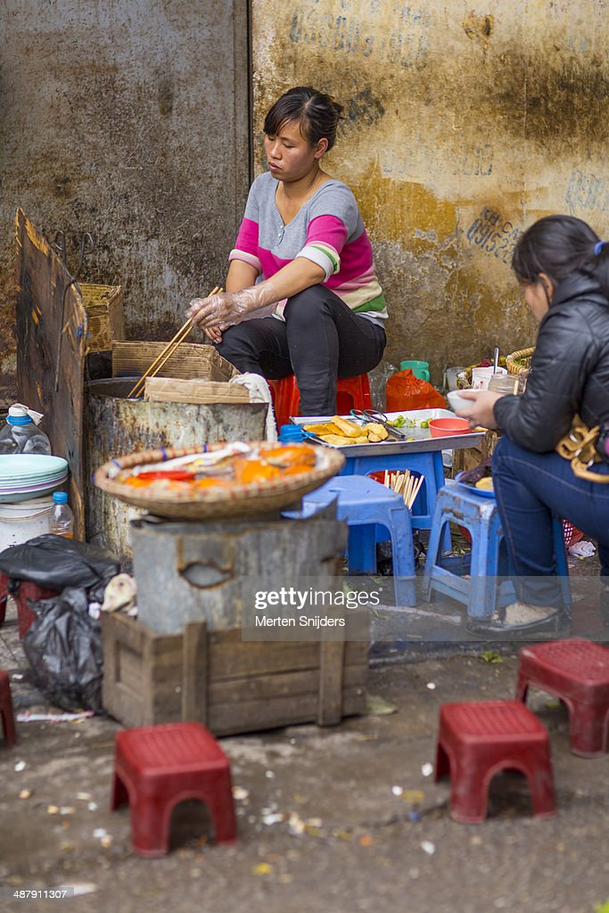Woman reaching in pan with chopsticks : Stockfoto