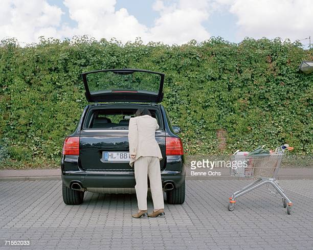 Woman reaching into car trunk with full shopping cart nearby