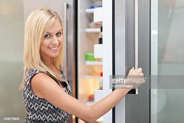Woman reaching into fridge