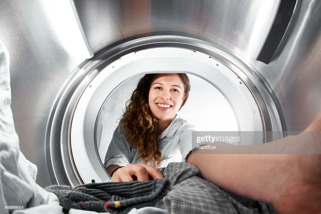 Woman reaching into tumble dryer, seen from inside : Stock Photo