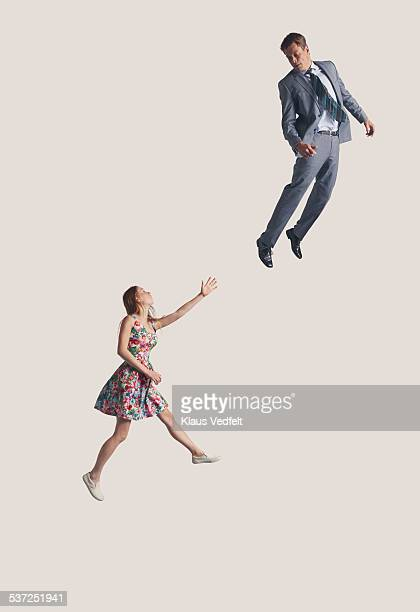 woman reaching out at businessman in the air - in de lucht zwevend stockfoto's en -beelden