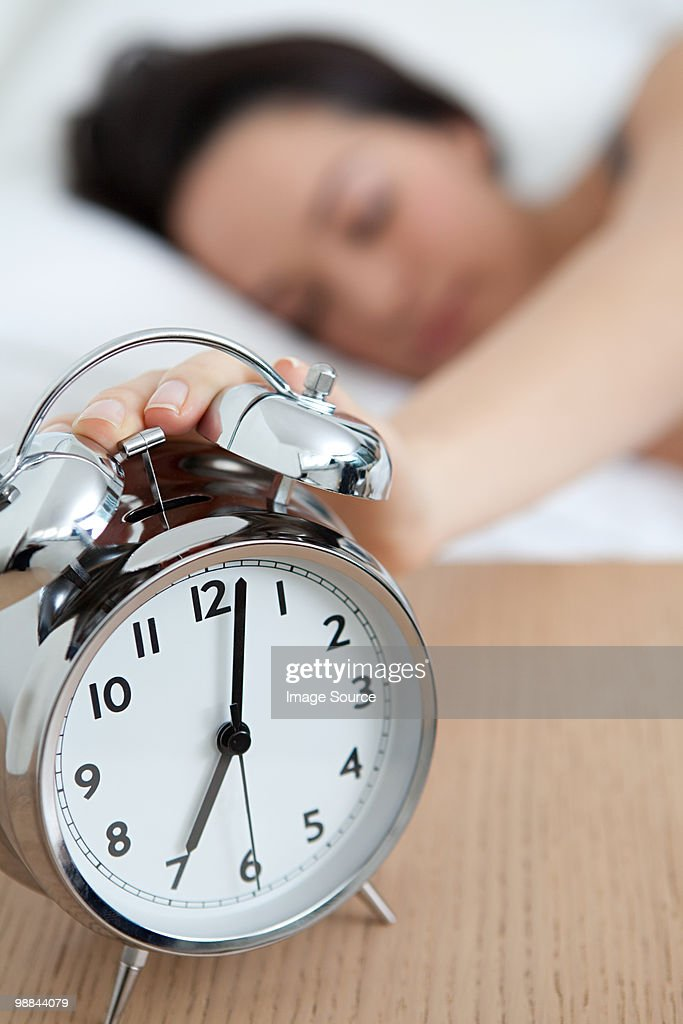 Woman reaching out for alarm clock : Stock Photo