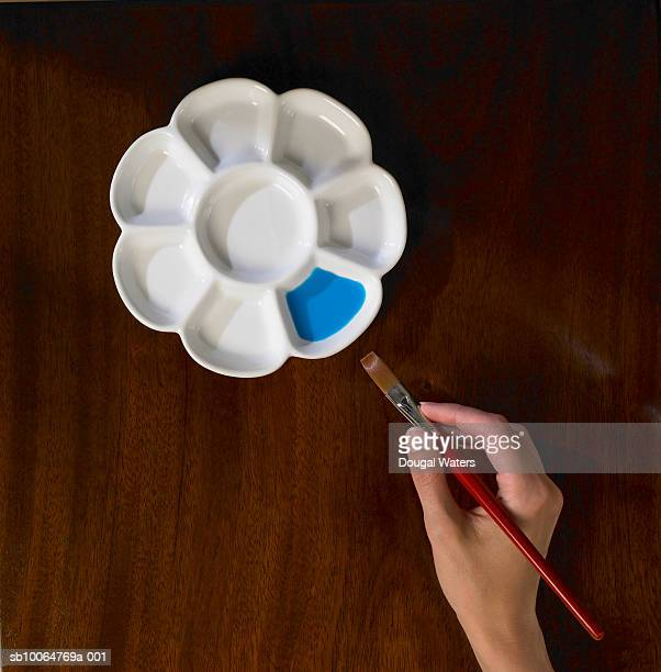 Woman reaching paint brush for pallet on table, close up of hand