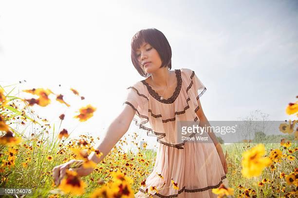 woman reaching to pick wild flowers near riverside - health2010 ストックフォトと画像