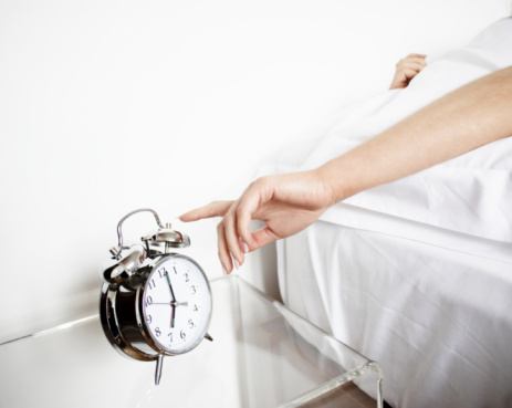 Woman reaching to turn off alarm clock - gettyimageskorea