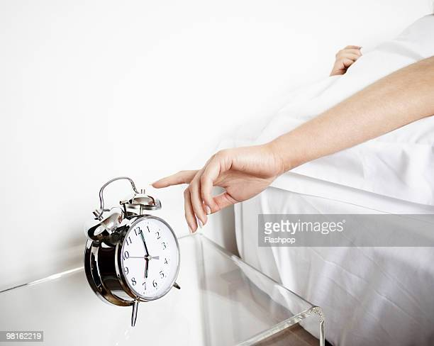 woman reaching to turn off alarm clock - routine stock-fotos und bilder