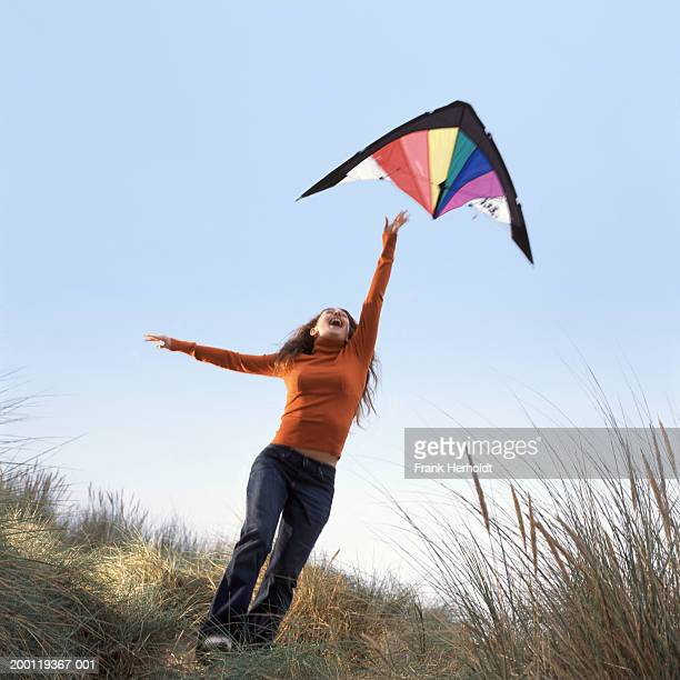 woman reaching up to kite in sky - kite toy stock photos and pictures
