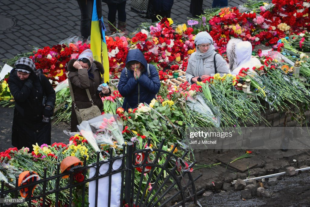 Woman react as they leave flowers in Independence Square where dozens of protestors were killed in clashes with riot police last week on February 25, 2014 in Kiev, Ukraine. Ukraine's interim President Olexander Turchynov is due to form a unity government, as UK and US foreign ministers meet to discuss emergency financial assistance for the country.