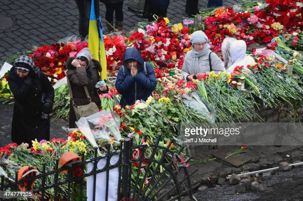 Woman react as they leave flowers in Independence Square where dozens of protestors were killed in clashes with riot police last week on February 25...
