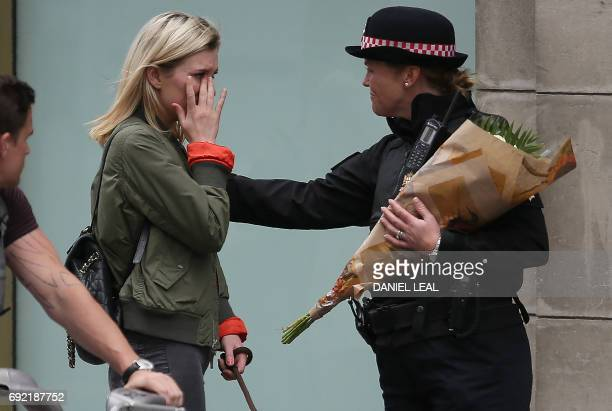 TOPSHOT A woman reacts after asking a Police officer to lay flowers near London Bridge in London on June 4 as a tribute to the victims of the June 3...