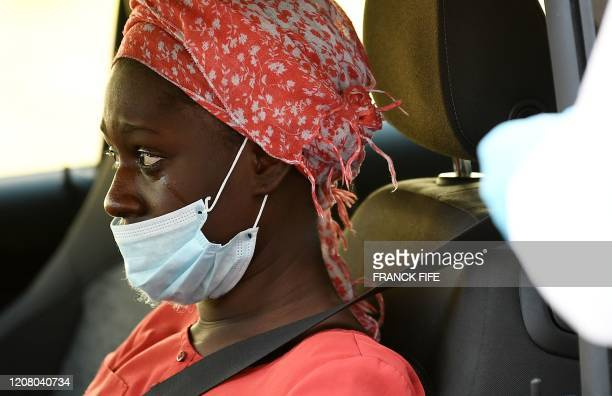 Woman reacts after having a sample collected at a COVID-19 screening-drive, in Lisses, south of Paris, on March 23 on the seventh day of a lockdown...