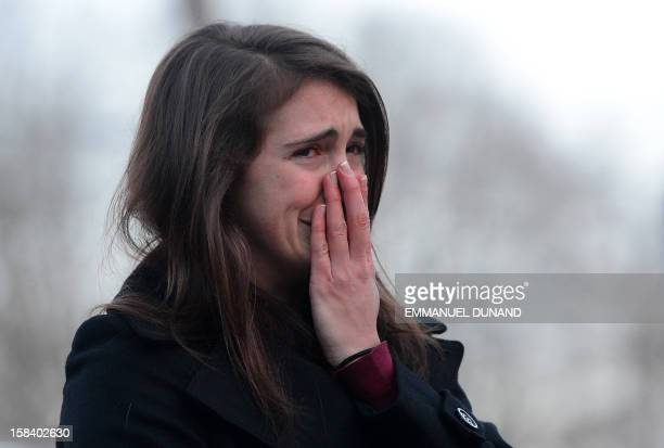A woman reacts after paying tribute to the victims of an elementary school shooting in Newtown Connecticut on December 15 2012 A young gunman...