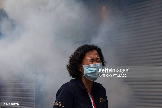 TOPSHOT A woman reacts after riot police fired tear gas to disperse protesters taking part in a prodemocracy rally against a proposed new security...