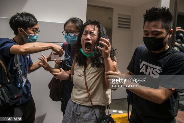 Woman reacts after she was hit with pepper spray deployed by police as they cleared a street with protesters rallying against a new national security...