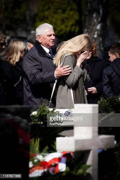 A woman reacts after visiting a grave of a victim of the 2010 Smolensk government plane crash at the Powazki military cemetery in Warsaw Poland on...