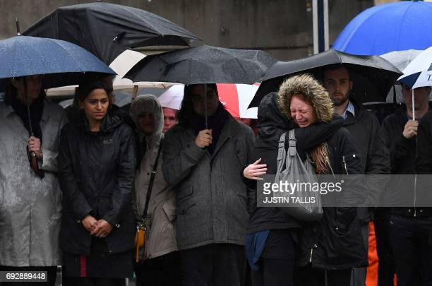 A woman reacts as people observe a minutes' silence at southside of London Bridge in London on June 6 in memory of the victims of the June 3 terror...