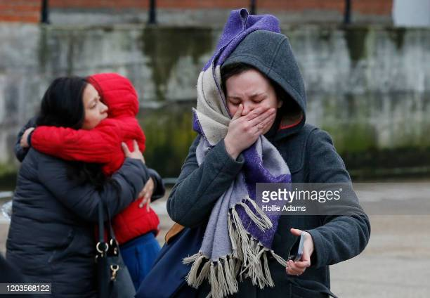 A woman reacts as police officers interview people near to the scene where a man was shot and killed by armed police on February 2 2020 in London...