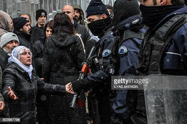 A woman reacts as police officers stand guard on December 31 2015 in Diyarbakir during a demonstration after a curfew was lifted from the city A...