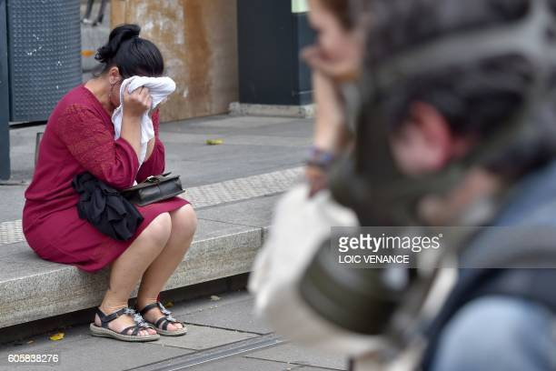 TOPSHOT A woman reacts as police use tear gas during a demonstration against the controversial labour reforms of the French government in Nantes...