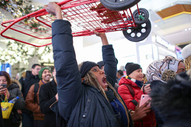 A woman reacts as she carries a shopping cart while customers arrive to the Macy's store on 33th street as Black Friday sales start early on November...