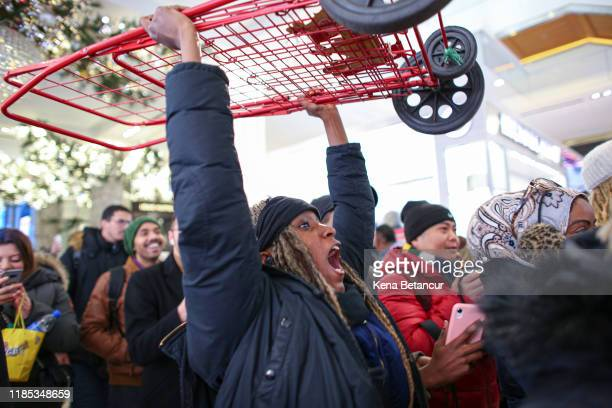Woman reacts as she carries a shopping cart while customers arrive to the Macy's store on 33th street as Black Friday sales start early on November...