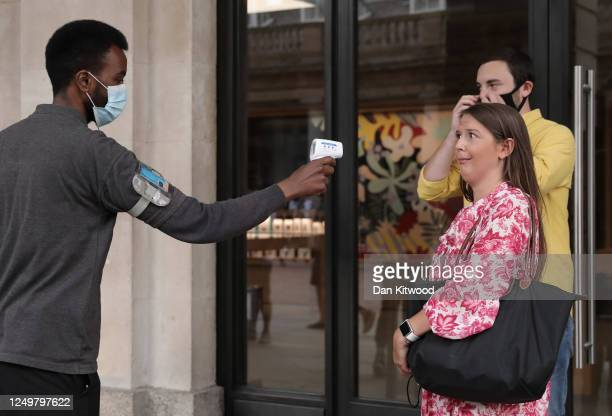 A woman reacts as she gets her temperature checked outside the Apple store in Covent Garden on June 15 2020 in London United Kingdom The British...