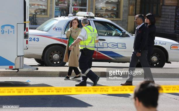 Woman reacts as she is brought to an ambulance to identify a victim after 10 people were killed and 15 people injured in a deadly van attack in...