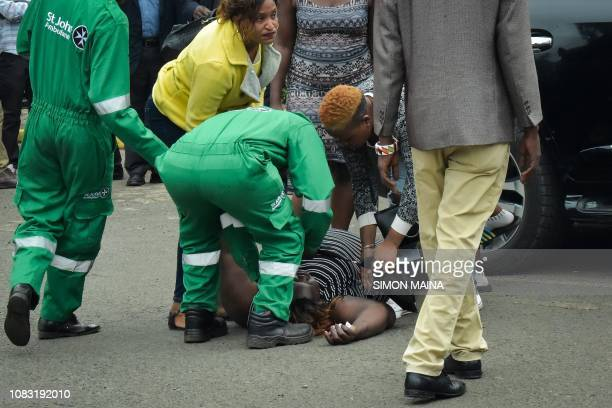 A woman reacts as she is helped by Saint John ambulance crew members in Nairobi on January 16 while identifying the bodies of the victims after a...