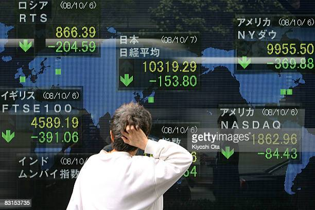 A woman reacts as she looks at an electronic board displaying the current Nikkei share average on October 7 2008 in Tokyo Japan The 225issue Nikkei...