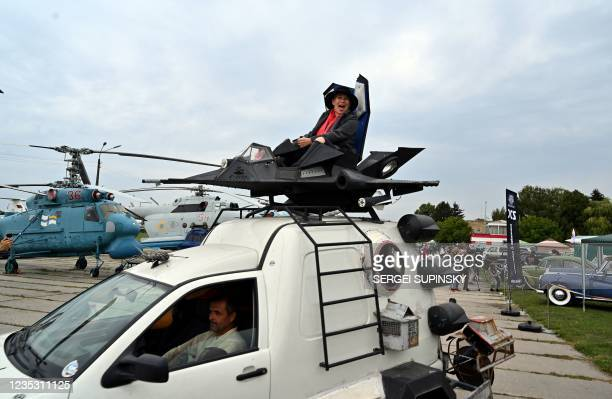 Woman reacts as she rides on top of a vehicle during OldCarLand festival at the open-air State Aviation Museum in Kiev on September 17, 2021.