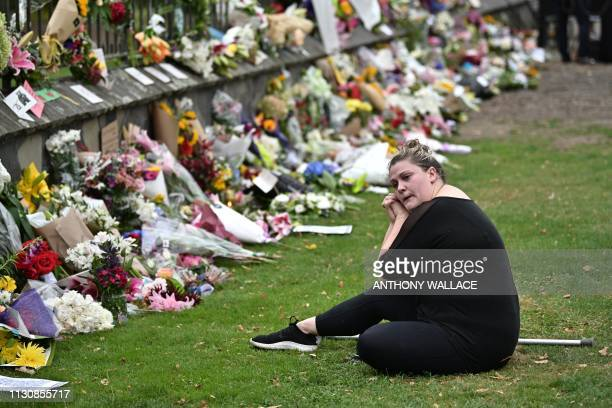 TOPSHOT A woman reacts as she sits among flowers left in tribute to victims outside the entrance of the hospital in Christchurch on March 16 after a...