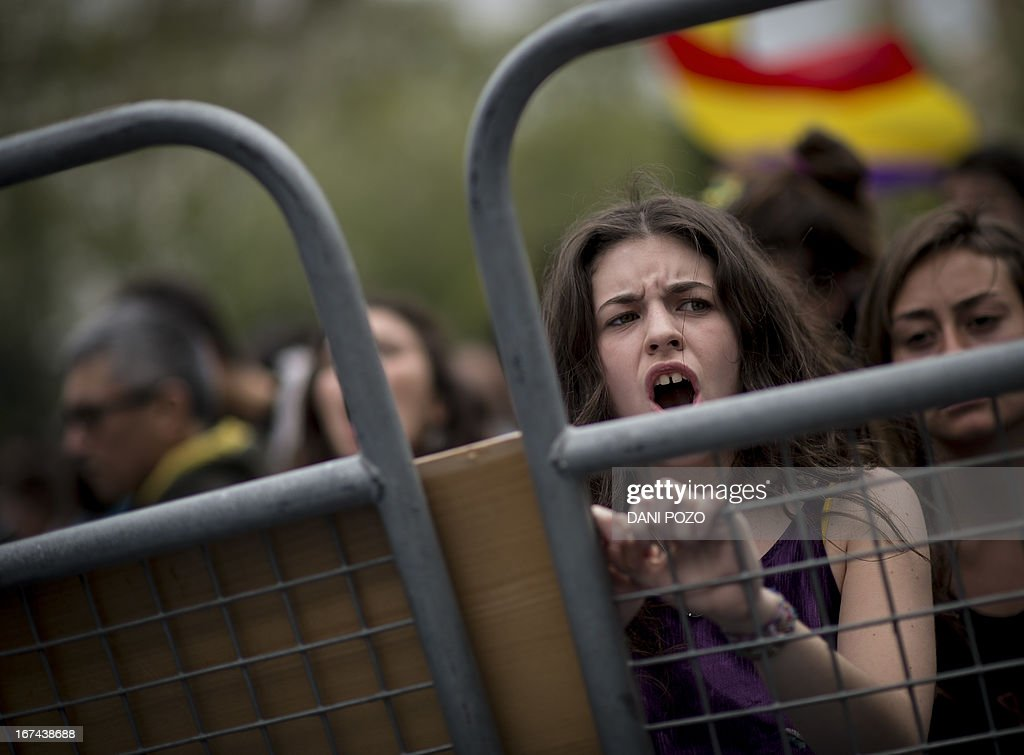 A woman reacts as she stands in front of fences blocking the street leading to the Spain's parliament (Las Cortes) during an anti-government demonstration in Madrid on April 25, 2013. A thousand of people, mostly youths, gathered today evening near the Spanish parliament in Madrid in response to a call by a hardline protest movement for demonstrators to 'Besiege Congress' indefinitely to force the government to quit.