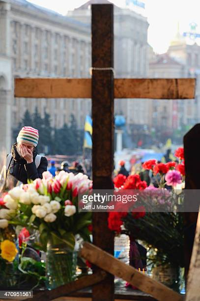 A woman reacts at a make shift shrine to the anti government demonstrators killed in yesterday's clashes with police in Independence square on...