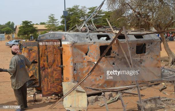 A woman reacts beside a burnt container on November 13 in Gao after a suicide car bomb attack overnight which killed three people Three Malian...