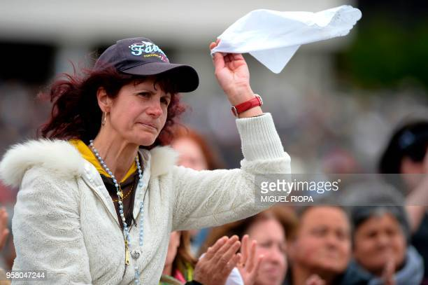 A woman reacts during a mass ceremony at the Fatima shrine in Fatima central Portugal on May 13 2018 Thousands of pilgrims converged on the Fatima...