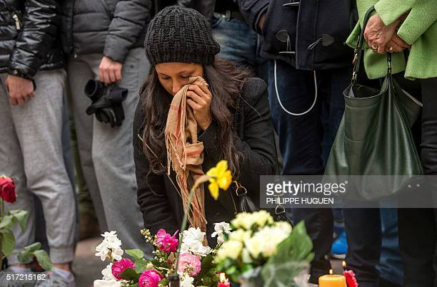 TOPSHOT A woman reacts during a minute of silence held at a makeshift memorial in front of Brussel's Stock Exchange on Place de la Bourse on March 24...