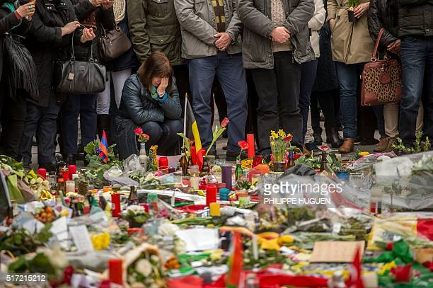 Woman reacts during a minute of silence held at a makeshift memorial in front of Brussel's Stock Exchange on Place de la Bourse on March 24 two days...