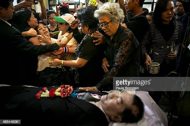 A woman reacts emotionally as hundreds of mourners pay their respects over the body of Sutin Tharatin a core antigovernment leader who was killed by...
