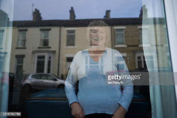 A woman reacts from her window as she watches residents of Coral Street in Saltburn come out of their homes at 6pm each evening to take part in Sing...