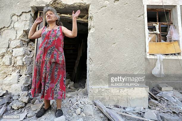A woman reacts in front of her house destroyed as a result of shelling between Ukrainian forces and proRussian separatists on August 10 2015 in...