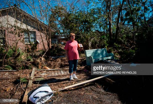 A woman reacts in her front yard in her newly renovated home that was destroyed by a storm surge in Port St Joe Florida on October 13 three days...