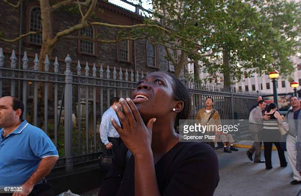 A woman reacts in terror as she looks up to see the World Trade Center go up in flames September 11 2001 in New York City after two airplanes slammed...