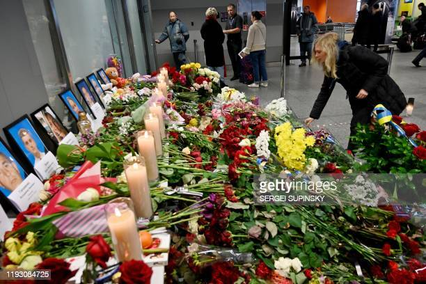 A woman reacts lays flowers at a makeshift memorial at the Boryspil airport outside Kiev on January 11 as she pays tribute for the victims of the...