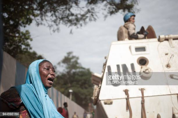 TOPSHOT A woman reacts next to UN soldiers as inhabitants of the mainly Muslim PK5 neighbourhood demonstrate in front of the headquarters of MINUSCA...