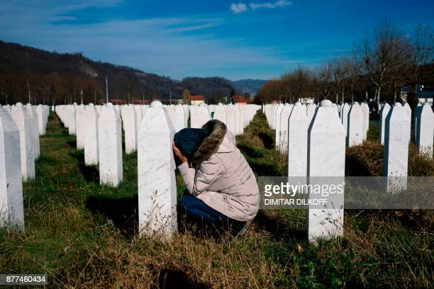 A woman reacts over a relative's grave at the memorial centre of Potocari near Srebrenica on November 22 2017 United Nations judges on November 22...